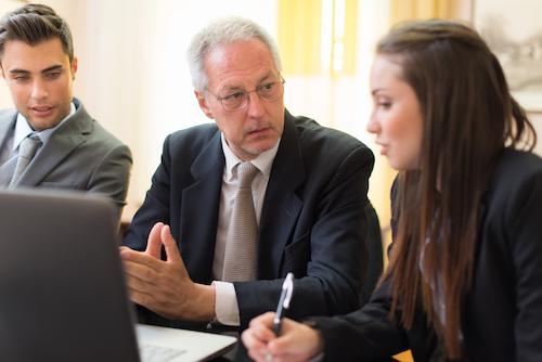Unternehmer bespricht sich mit seinen Mitarbeitern, weil er die Firma verkaufen möchte.