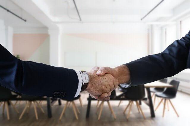 Zwei Männer schütteln sich die Hände beim Firmenverkauf