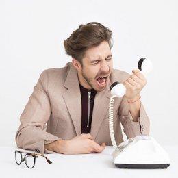 Mann schreit in den Telefonhörer - Nachfolge in Famlienunternehmen