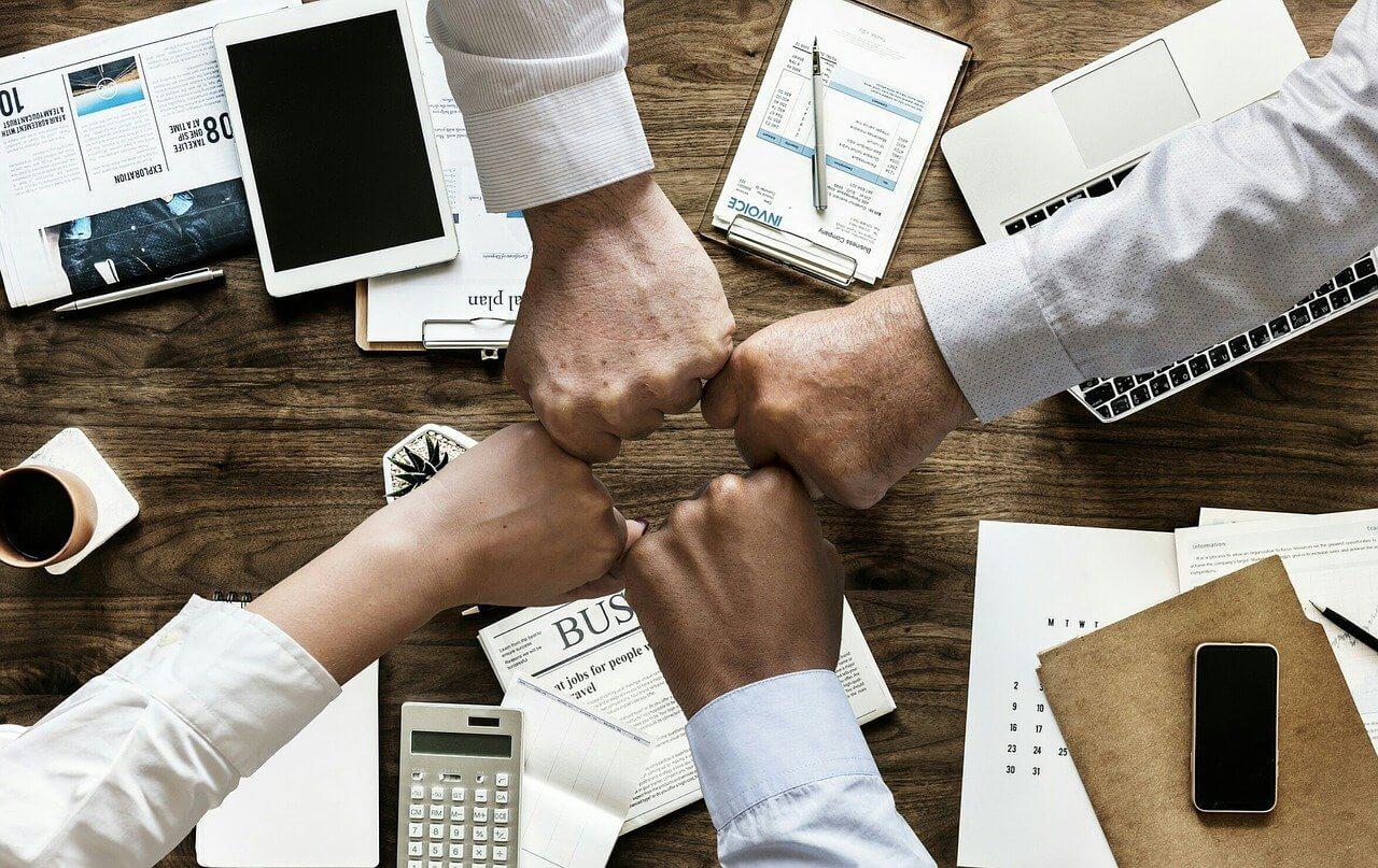 Fäuste zusammen als Zeichen für einen erfolgreichen Management Buy Out als Team.
